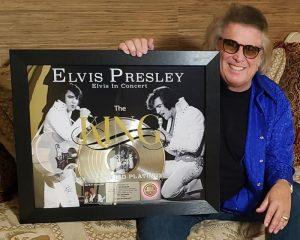 Don McLean holding Elvis Presley award plaque