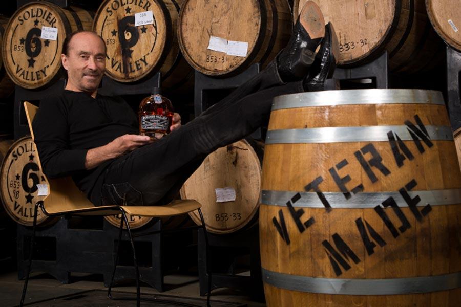 Lee Greenwood holding a bourbon bottle